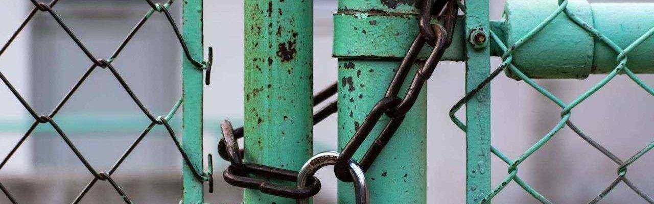 A green gate locked with a chain and padlock